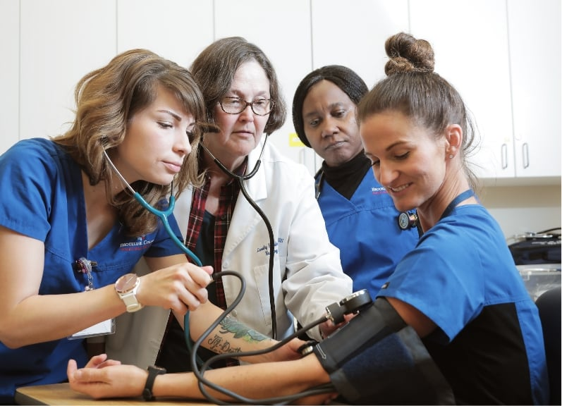Three students practicing collecting vitals on each other with the help of an instructor
